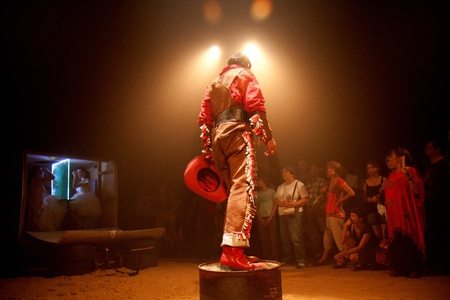 petrol can: AURILLAC, Francia - 22 de agosto: un vaquero se encuentra en una lata de gasolina en medio de una gran carpa, Aurillac International Street Festival de Teatro, Compa��a Off, el 22 de agosto de 2012, en Aurillac, Francia.