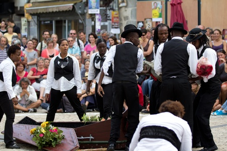 AURILLAC, FRANCE - AUGUST 24: actors carrying a woman towards a coffin, Aurillac Street Theater Festival,  Brigade d'intervention th��trale Ha�tienne, on august 24, 2012, in Aurillac,France. Stock Photo - 15102225