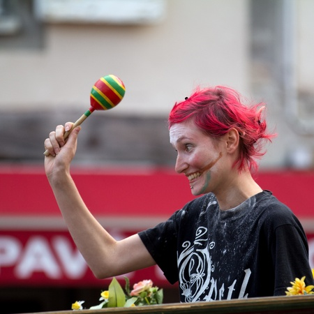 AURILLAC, FRANCE - AUGUST 24: a spectator is holding a hochet, Aurillac International Street Theater Festival,  Brigade d'intervention th��trale Ha�tienne, on august 24, 2012, in Aurillac,France. Stock Photo - 15102218