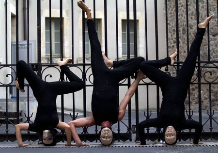 diagonale: AURILLAC, FRANCE - AUGUST 23: actors upside down in the street as part of the Aurillac International Street Theater Festival, show La diagonale du Fou, on august 23, 2012, in Aurillac,France.