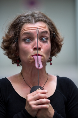 AURILLAC, FRANCE - AUGUST 22: a woman is passing a metal rod trough her tongue, Aurillac International Street Theater Festival,by the Cabinet du bon Docteur No, on august 22, 2012, in Aurillac,France.