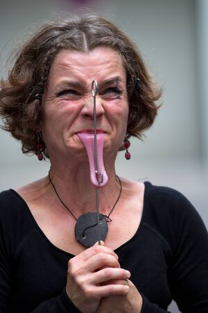 AURILLAC, FRANCE - AUGUST 22: a woman is grimacing in pain as part of the Aurillac International Street Theater Festival,show by the Cabinet du bon Docteur No, on august 22, 2012, in Aurillac,France. Stock Photo - 15131873