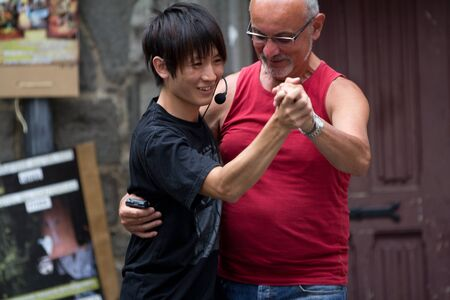 AURILLAC, FRANCE - AUGUST 24: an actor dances with a spectator in the street as part of the Aurillac International Street Theater Festival, show Robot Nozomi, on august 24, 2012, in Aurillac,France. Stock Photo - 15131875