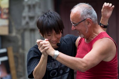 AURILLAC, FRANCE - AUGUST 24: Two men dance in the street as part of the Aurillac International Street Theater Festival, show Robot Nozomi, on august 24, 2012, in Aurillac,France. Stock Photo - 15131874
