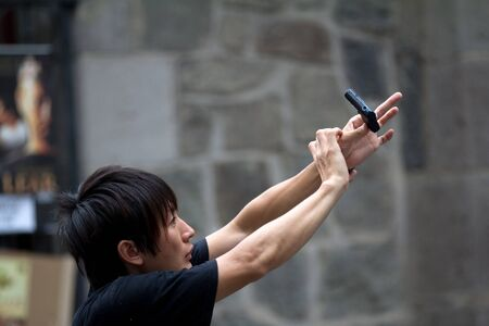 cantal: AURILLAC, FRANCE - AUGUST 24: an actor is holding a gun in the street as part of the Aurillac International Street Theater Festival, show Robot Nozomi, on august 24, 2012, in Aurillac,France. Editorial