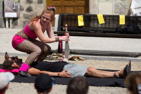 AURILLAC, FRANCE - AUGUST 23: An actress holds a big knife above a spectator as part of the Aurillac International Street Theater Festival, show by Stacy Trong, on august 23, 2012, in Aurillac,France. Stock Photo - 15131889