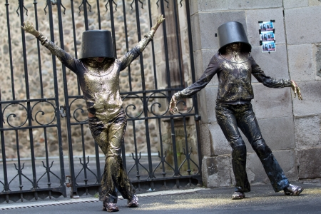 AURILLAC, FRANCE - AUGUST 23: Two women dance with a bucket on the head as part of the Aurillac International Street Theater Festival, show named Vachement, on august 23, 2012, in Aurillac,France. Stock Photo - 15131907