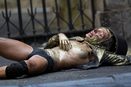AURILLAC, FRANCE-AUGUST 23: a dirty and naked dancer is lying on the ground as part of the Aurillac International Street Theater Festival, show named Vachement, on august 23, 2012, in Aurillac,France. Stock Photo - 15131901