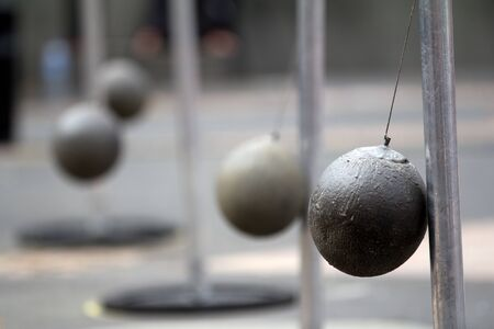 cantal: AURILLAC, FRANCE - AUGUST 24: four heavy balls swinging in the street as part of the Aurillac International Street Theater Festival, show named New town, on august 24, 2012, in Aurillac,France.