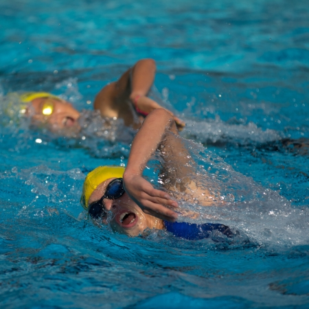 AUCH, FRANCE - SEPTEMBER 8: two unidentified young swimmers in the pool, Auch Triathlon for children, on September 8, 2012 in Auch, France. Editorial