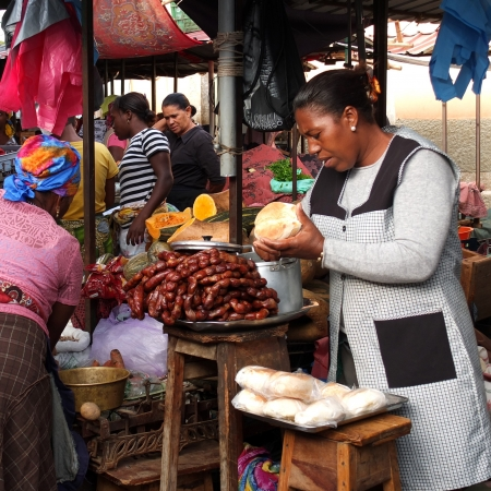 praia: Praia, Cape Verde - December 6, 2012: an African woman cooks at the market. Editorial