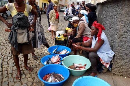 Assomada, Cape Verde - December 5, 2012: an African fish vendor is waiting for buyers in the street. She has fishes in some basins.