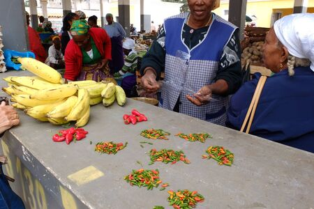 Assomada, Cape Verde - December 5, 2012: African market, bananas and hot chilis to sell. Stock Photo - 16870104