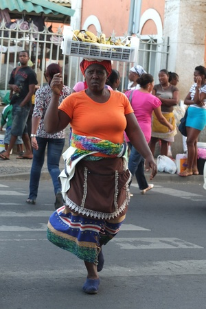 Praia, Cape Verde - December 4, 2012: a woman is crossing the street. She is balancing a basket of bananas on her head.