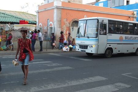 Praia, Cape Verde - December 4, 2012: A woman is crossing a large street. She is carrying boxes on her head. On the right, there is an old white bus.
