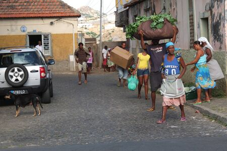 Praia, Cape Verde - November 26: some African people is carrying goods to sell at the market.Everyone is coming on foot.