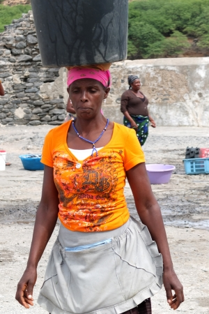 Tarrafal, Cape Verde - November 29, 2012: An African woman is carrying a black bin on her head. Stock Photo - 16978934