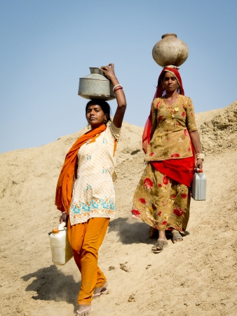 JAISALMER,  INDIA - MARCH 8: Close-up portrait of two women carrying  water in the desert , March 8, 2013, Jaisalmer, India. They are walking on a dune with heavy jugs on their heads.