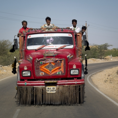 JAISALMER,  INDIA - MARCH 9: unidentified workers are transported in a typical red truck on March 9, 2013, Jaisalmer, India.  Stock Photo - 19309311