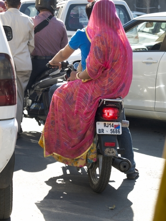 JAIPUR,  INDIA - MARCH 5: an unidentified woman is sitting side-saddle on a motor cycle in the center of the city, on March 5, 2013, Jaipur, India. She is wearing a pink sari. Editorial