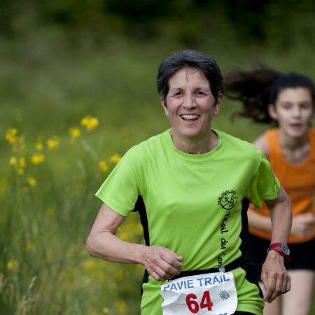 PAVIE, FRANCE - JUNE 23: Elderly runner at the Trail of Pavie, on June 23, 2013, in Pavie, France.  She is smiling, Behind her, we can see a very young competitor.