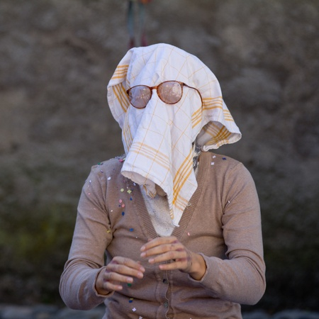 AURILLAC, FRANCE - AUGUST 21 an old woman wears a dish towel on the face as part of the Aurillac International Street Theater Festival, Company L arbre à vache ,on august 21, 2013, in Aurillac,France Redakční