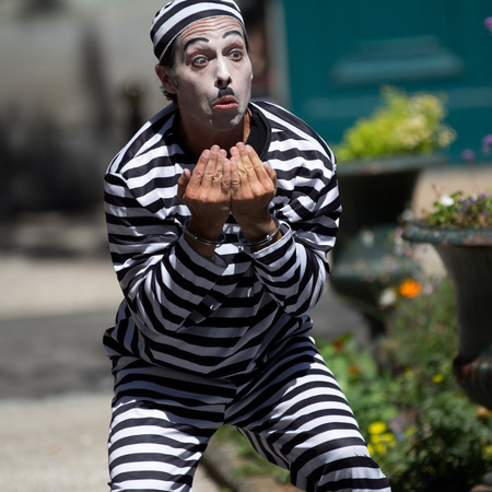 AURILLAC, FRANCE - AUGUST 21  handcuffed clown in the street as part of the Aurillac International Street Theater Festival, Company Les hommes papillon,on august 21, 2013, in Aurillac,France