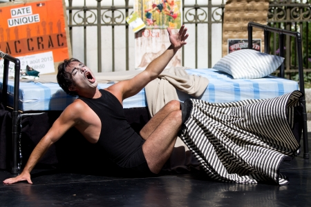 hommes: AURILLAC, FRANCE - AUGUST 21  an actor plays near a bed in the street as part of the Aurillac International Street Theater Festival, Company Les hommes papillon,on august 21, 2013, in Aurillac,France