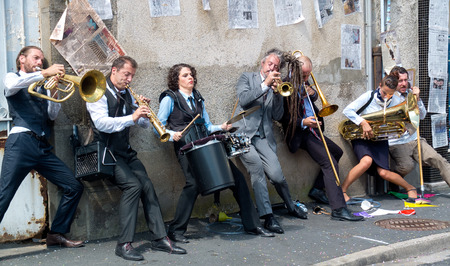 AURILLAC, FRANCE - AUGUST 23  Group of musicians playing against a wall, as part of the Aurillac International Street Theater Festival, cie Rhinofanpharyngite,on august 23, 2013, in Aurillac,France