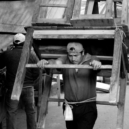 larger than life: CHICHICASTENANGO, GUATEMALA -  DECEMBER 1  A man is carrying  a big wooden table and some chairs on his back to the market , on December 1, 2013, in Chichicastenango, Guatemala