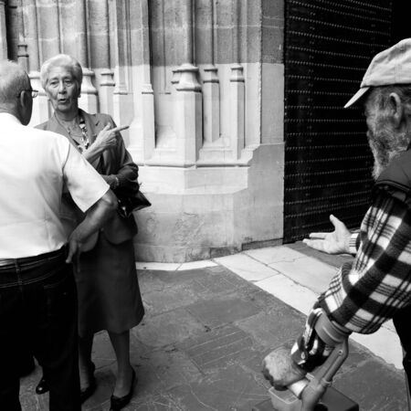 blak white: SEVILLE, SPAIN -  OCTOBER 19  At the end of the mass an old beggar ask for handouts at the exit of the cathedral , on October 19, 2013, in Seville, Spain