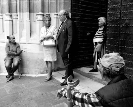 beggars: SEVILLE, SPAIN -  OCTOBER 19  At the end of the mass two old beggars ask for handouts at the exit of the cathedral , on October 19, 2013, in Seville, Spain    Editorial