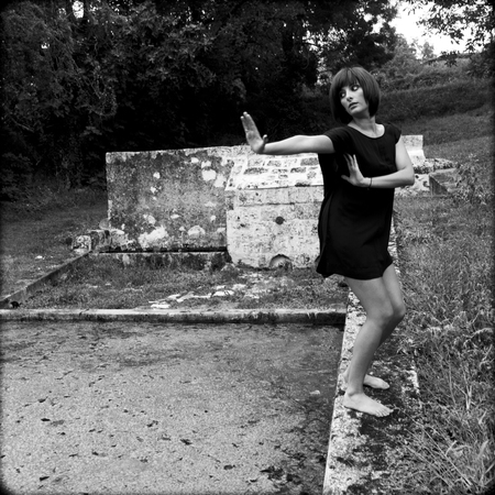 Beautiful woman on the edge of an old wash house  She raises her arms to repulse a supposed danger