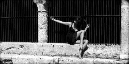 Sexy woman leaned against an old iron grille in Lectoure, Gers, France  She is barefoot and she wears a short black dress  photo