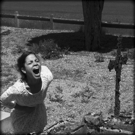 Woman in distress  She is yelling in a cemetery