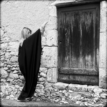 Very supple woman holding her foot very high along an old facade in Touget, Gers, France  She is blond and she wears a long black dress  photo