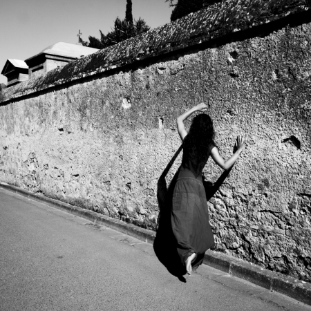 Brunette dancer moves barefoot along an old wall, in L Isle Jourdain, Gers, France