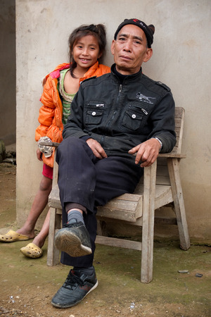 kindy: MUANG KHUA, LAOS -  JANUARY 29   A man is sitting on a wood chair with a smiling young girl near him in a street of the village, on January 29, 2014, in Muang Khua, Laos