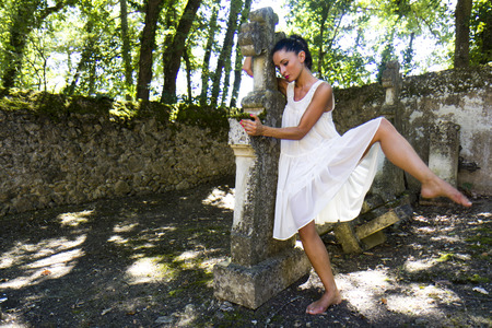 Serene image of a young woman who dances around a grave  She wears a white dress and she is barefoot  Stok Fotoğraf