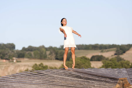 tiptoes: A young woman is balancing on the edge of a wooden structure named Yan�  She is on  tip-toes and she risks to fall down  She wears a white dress  Stock Photo