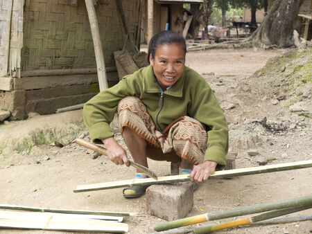 MUANG NGOI, LAOS -  JANUARY 26   A laotian woman cuts bamboo outside his home , on January 26, 2014, in Muang Ngoi, Laos