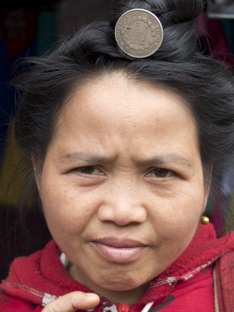 MUANG KHUA, LAOS -  JANUARY 29    Portrait of a Laotian woman wearing a silver french coin in her hair, on January 29, 2014, in Muang Khua, Laos