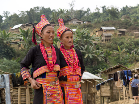 MUANG KHUA, LAOS -  JANUARY 30   Two Akha women wearing beautiful traditional costumes dance in their village, on January 30, 2014, in Muang Khua, Laos