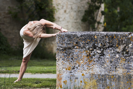 gascony: Stretching of a sporty blond woman  She is outdoors She wears white clothes  She is barefoot