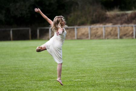 gascony: Rear view of a blond dancer jumping in a stadium  She wears white clothes  The lawn is very green