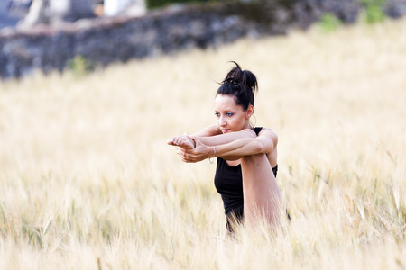 gascony: Contemporary dancer holding her foot with her hands  She is in the middle of a wheat field