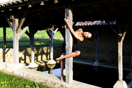 gascony: Graceful model hanged at the wooden pillar of an old wash house in France