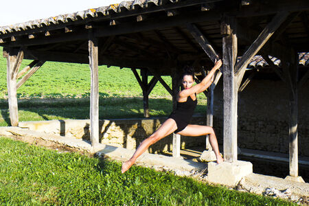 hanged woman: Graceful gymnast hanged at the wooden pillar of an old wash house in France