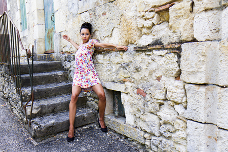 gascony: Contemporary dancer leaned against the wall of an old house in a french village  She wears a flowery short dress and high heels  Stock Photo