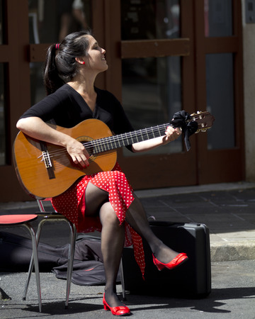 aurillac: AURILLAC, FRANCE-AUGUST 22: a young and cute spanish actress plays the guitar  as part of the  Aurillac International Street Theater Festival, cie Jean Faustin,on august 22, 2014, in Aurillac,France.